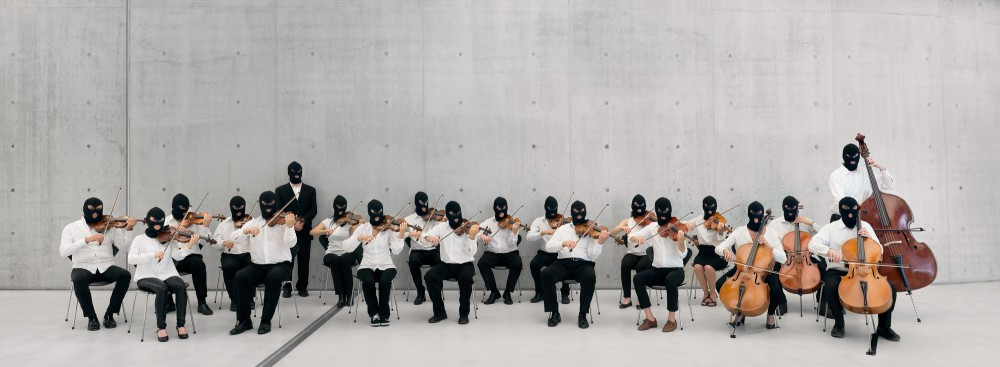 A string orchestra with 20 people. All musicians are wearing white shirt and black balaclava covering their face.