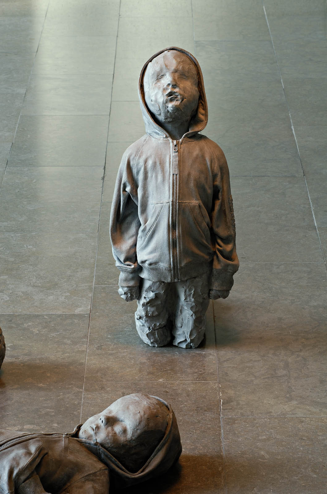 A child wearing a hood, on is knees looking upwards.