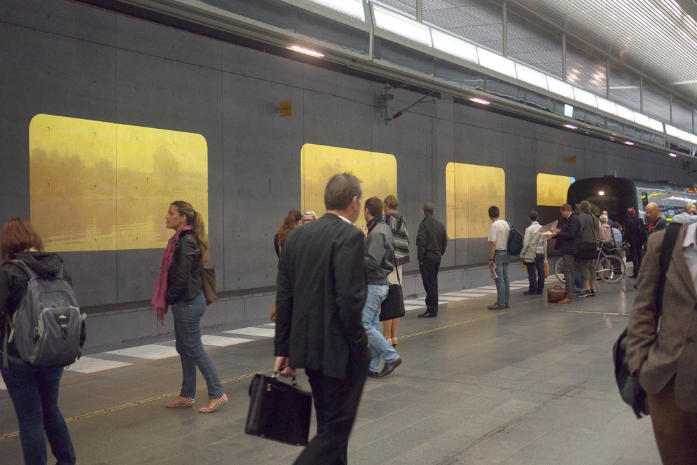 People waiting for the train. On the wall projections of water and trees.