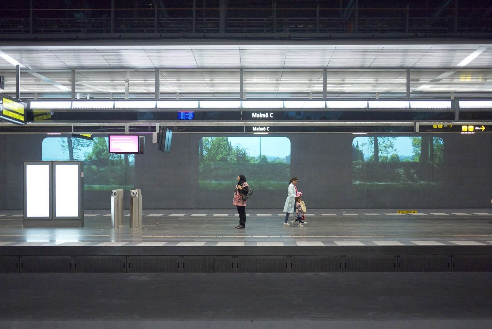 Two people on a platform. In the bakground three projections.