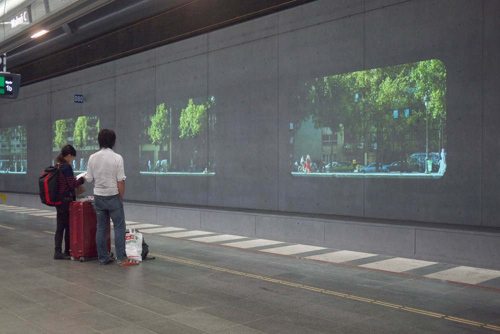 Two people with luggage looking at projections while waiting for the train.