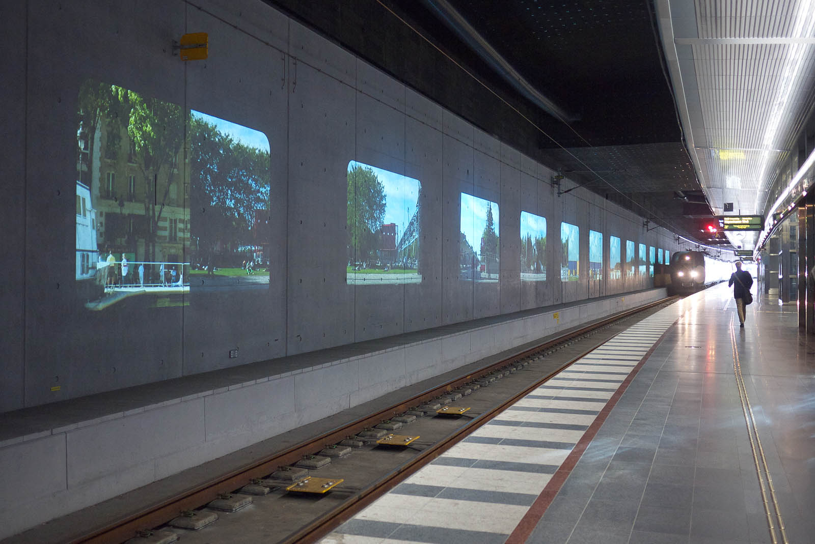 A train entering the station. On the wall projections of houses and trees.
