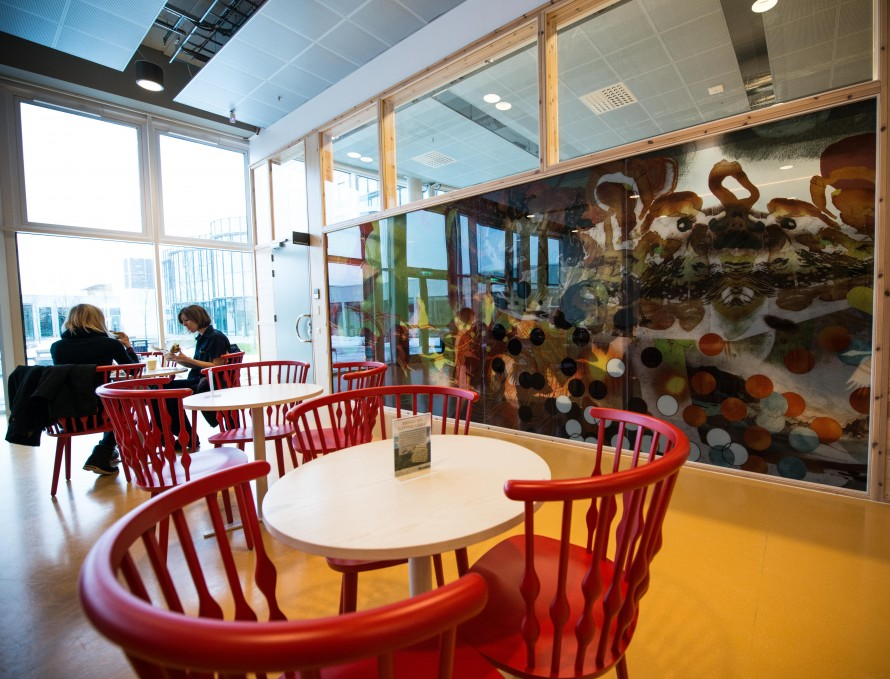 In the background a painted glass wall. In the front three tables with red chairs around them.