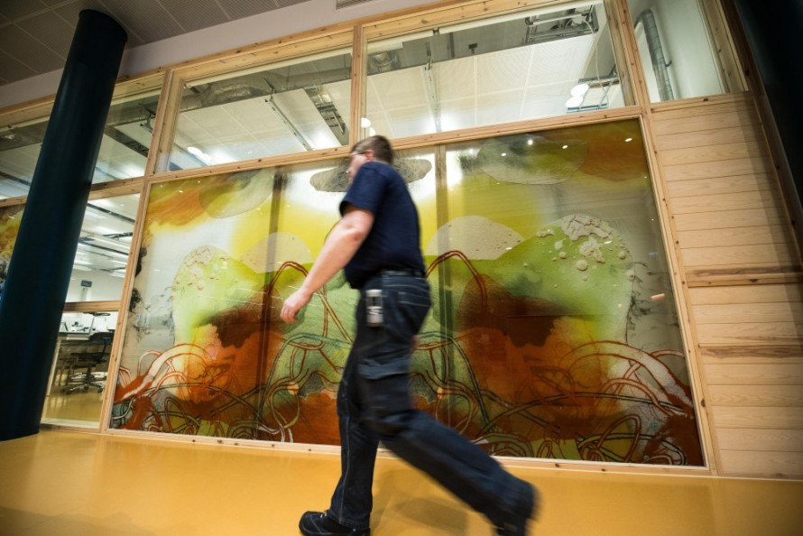 A man walking by a painted glass wall.