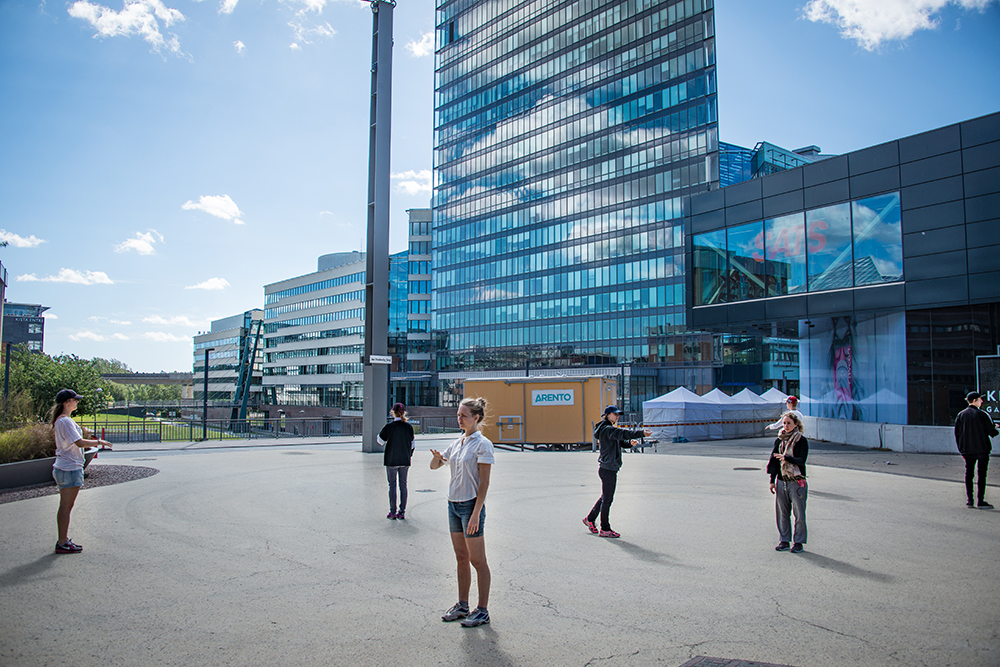 A group of peopela standing outside , each looking in their own direction. In the background a high-rise building.