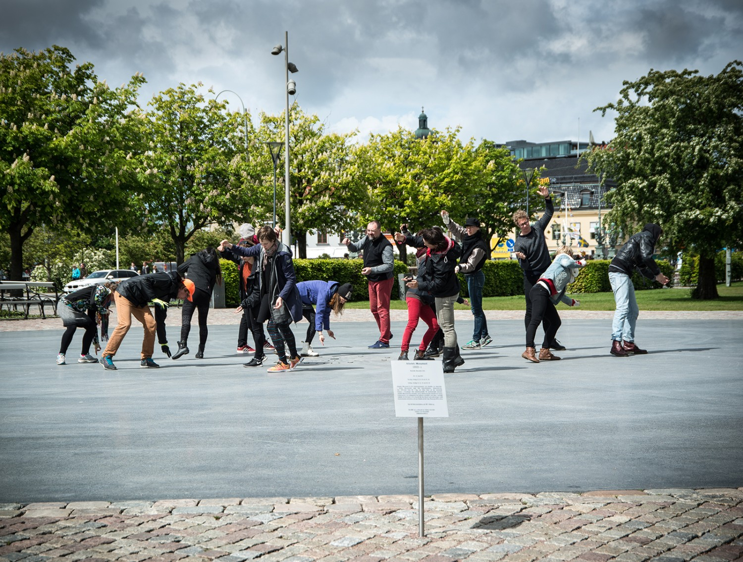A group of people in an open space All are leaning in various directions.