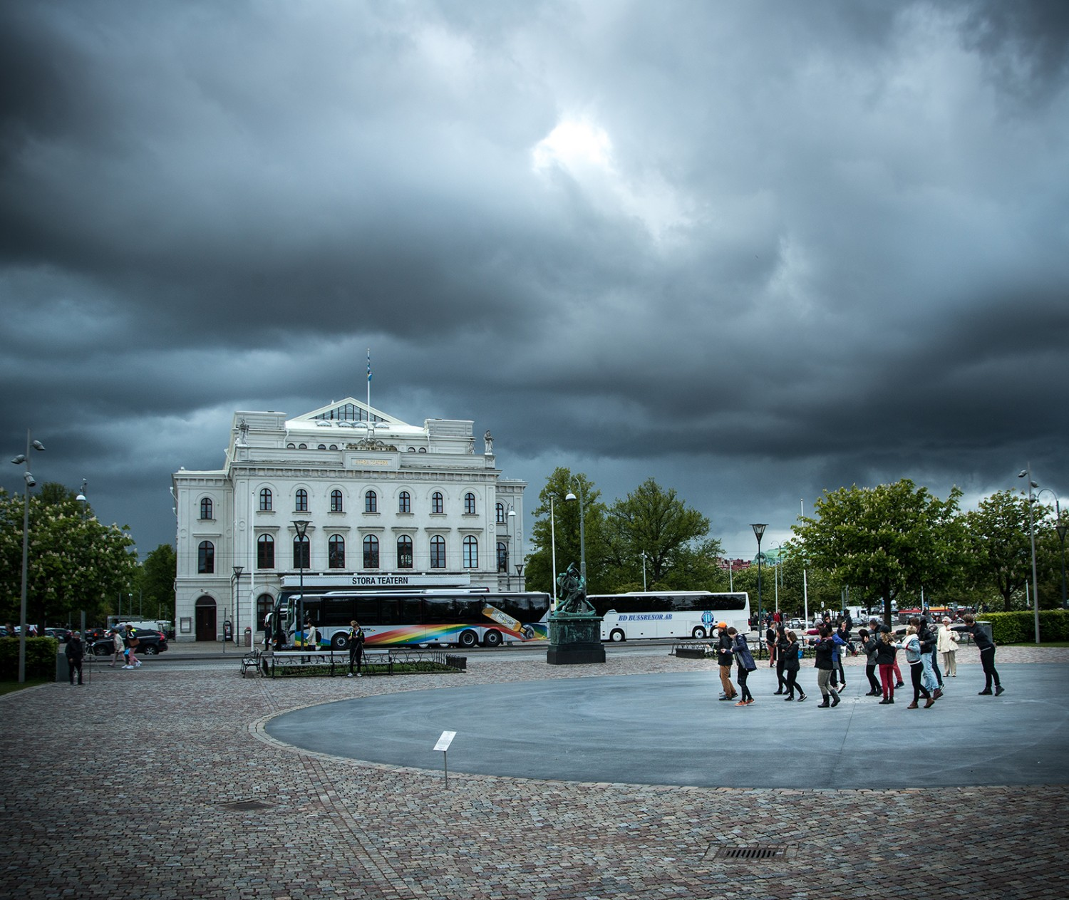 Clouds over Stora Teatern in Malmö. In the corner av the picture a group of people are making movements with their arms.