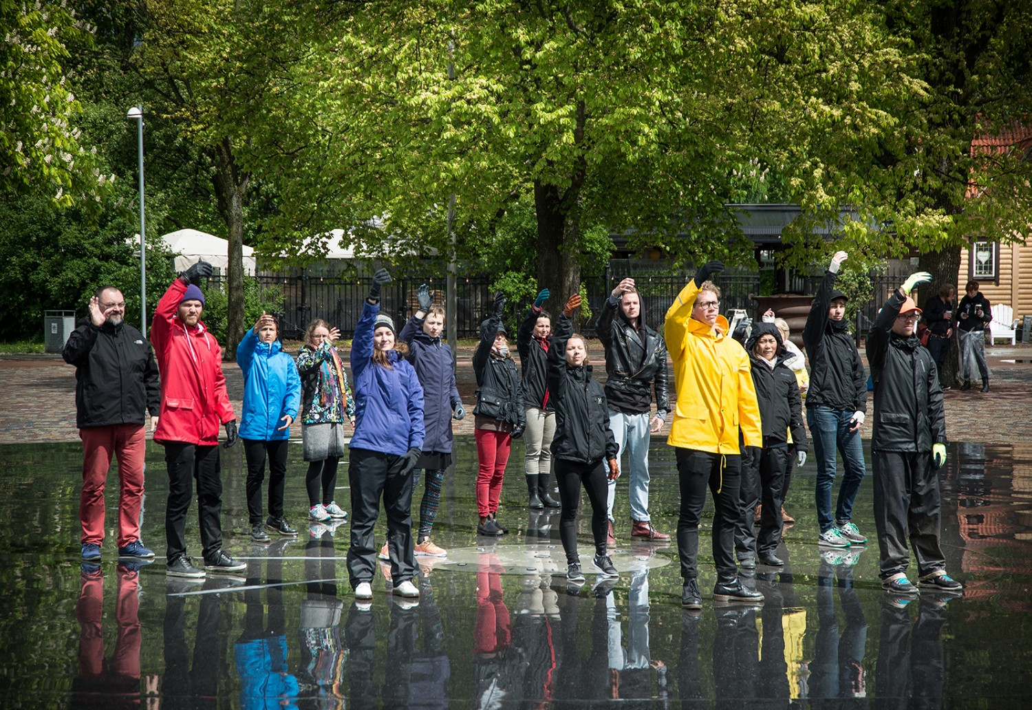 A group of peole in raincoats with their right arm raised.