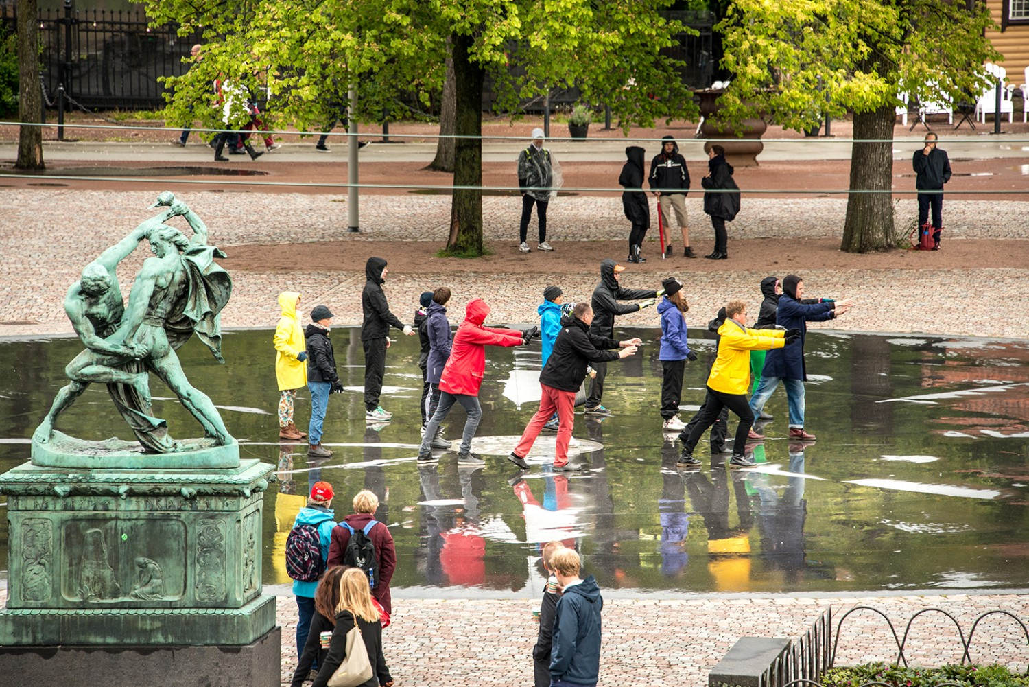 A group of people in raincoats. Each person is strectching out his arm.
