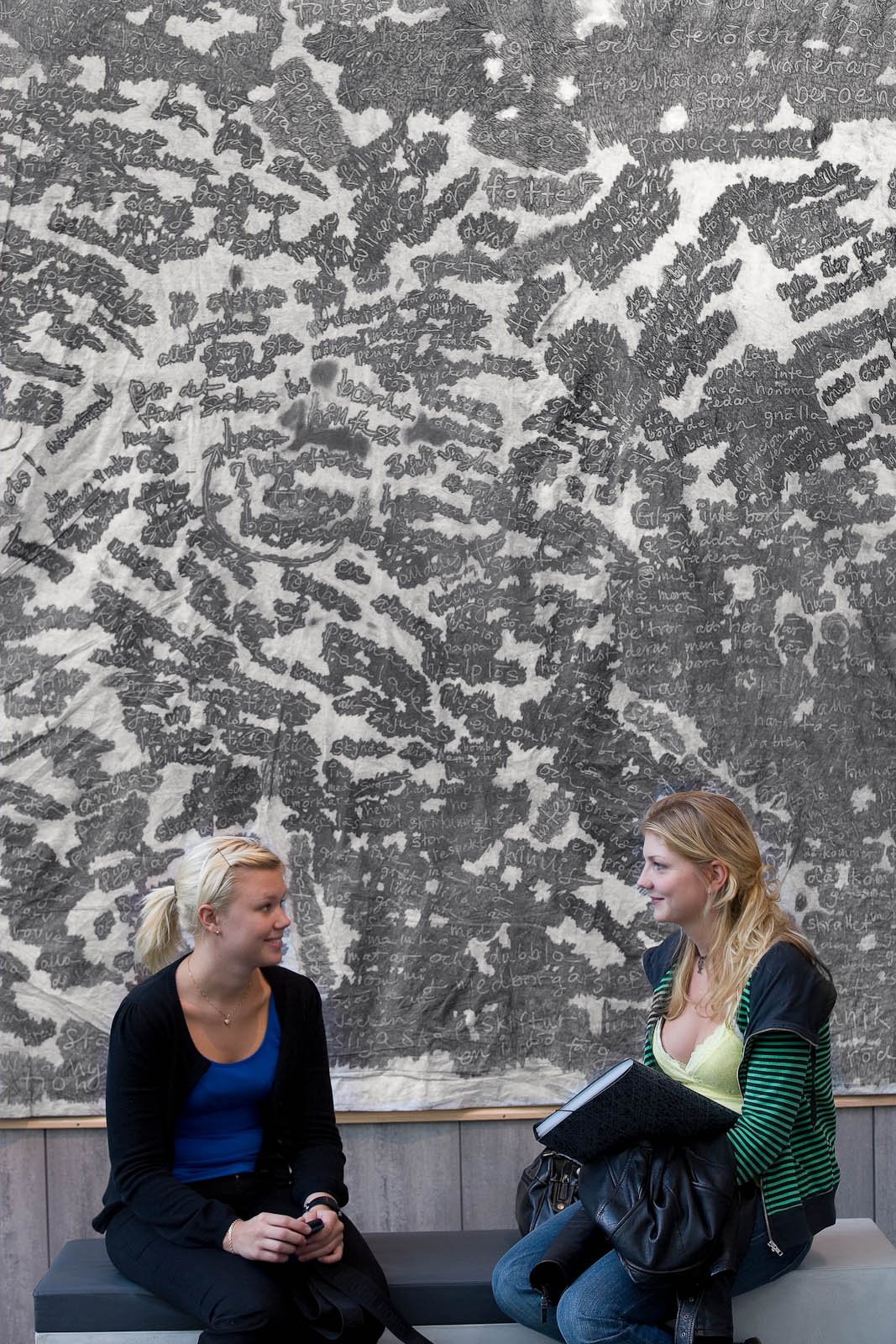 Two women sitting on a bench in front of the artwork.