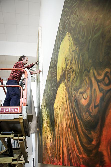 Två män i en skylift monterar en del av målningen på väggen. Danilo Stankovic, När fåglar tystna.