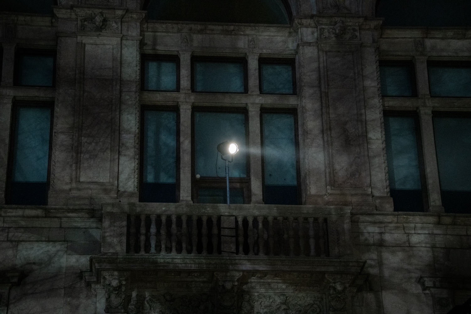 A lamp on the facade of the art academy in Stockholm. The picture is taken when it is dark and the lamp is shining.