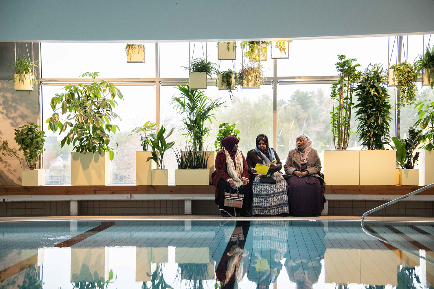An indoor swimming pool with several plants in the background and three sitting women.
