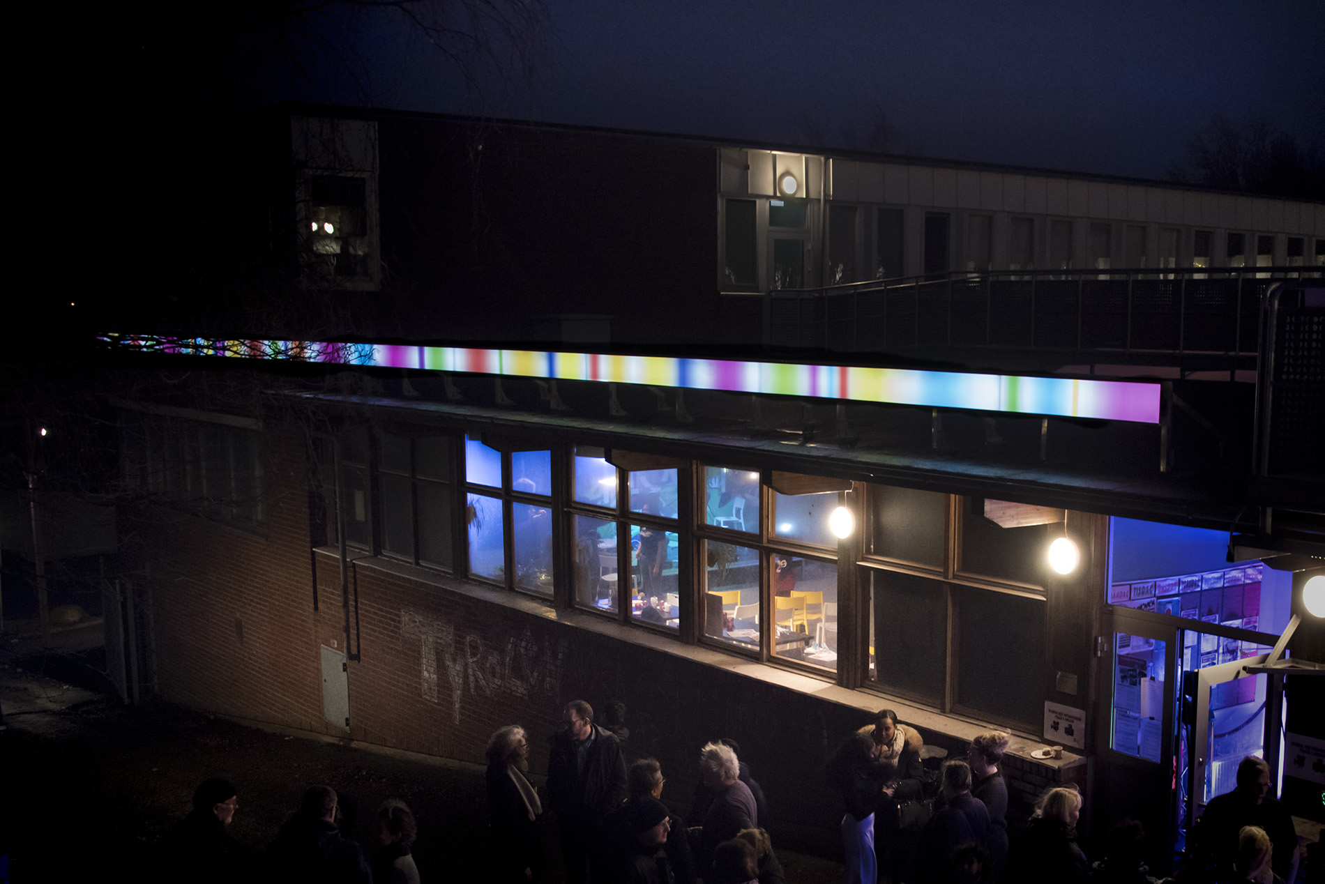 A series of light boxes running across the facade of a brick wall. Shot at night, when the artwork is light.