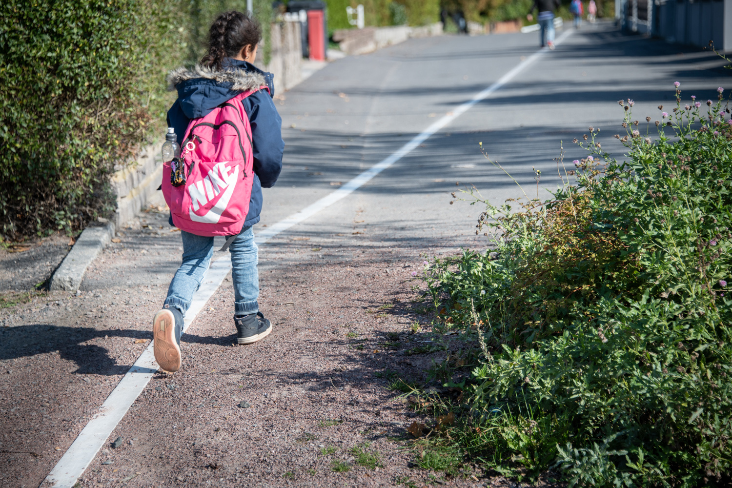 A girl with a backpack walks along a white line.