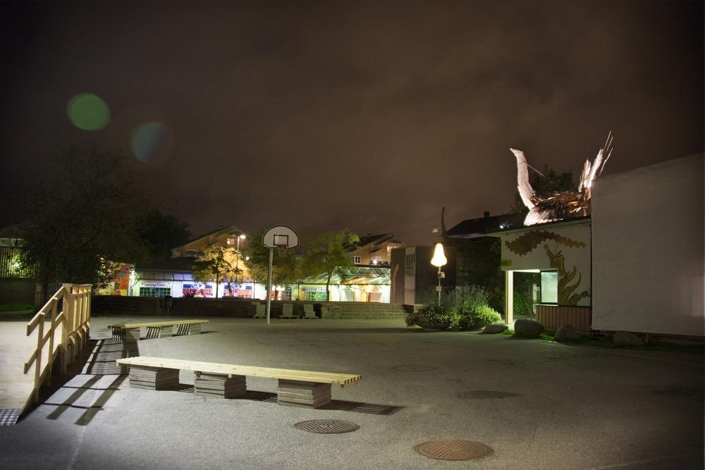 En sen höstkväll i Jordbro med vy över basketplanen utanför kulturhuset. Bakgrunden syns den lysande näsan och på husets tak tornar fågeln upp sig.