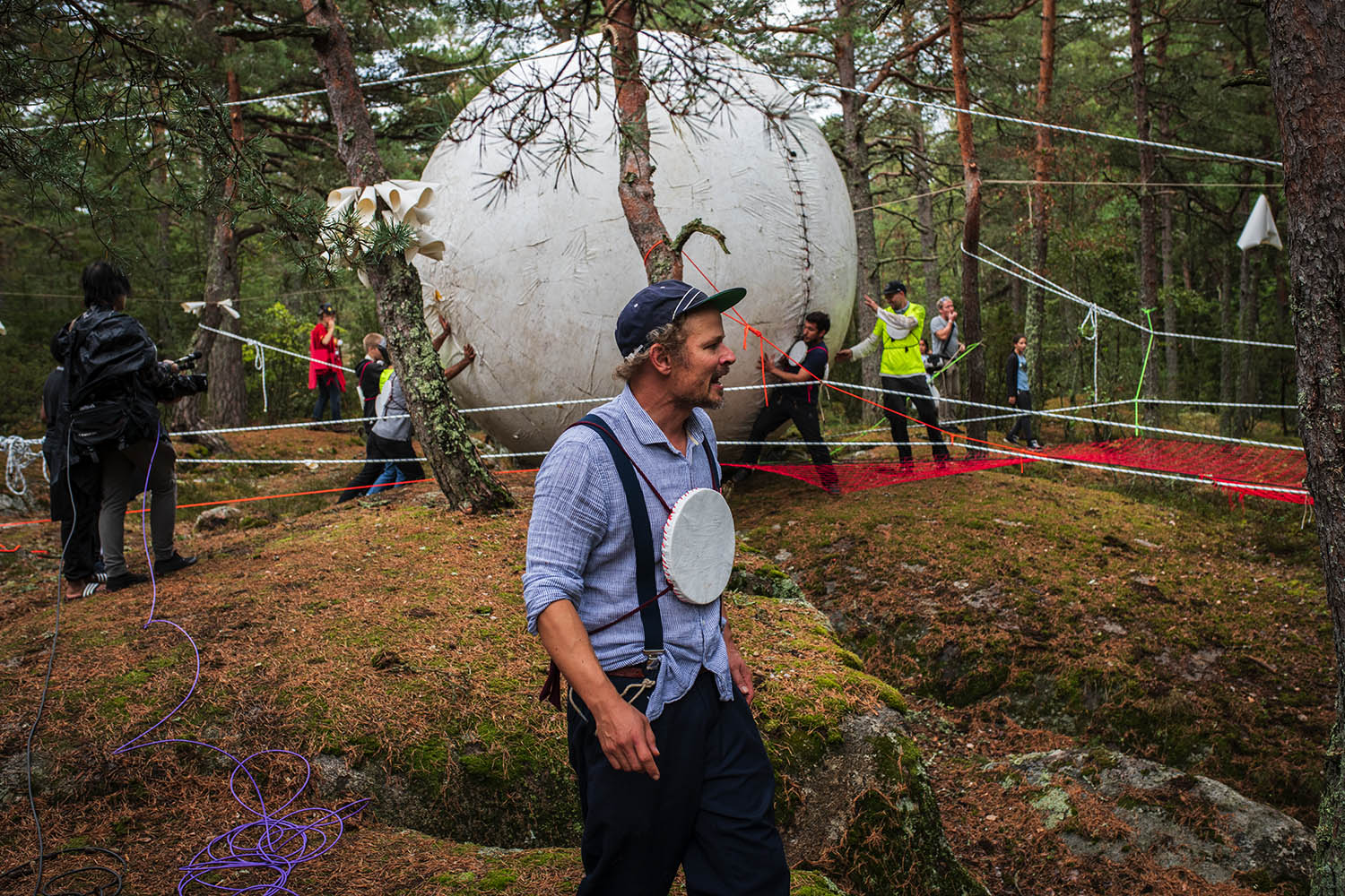 People rolling a giant ball in the forrest.