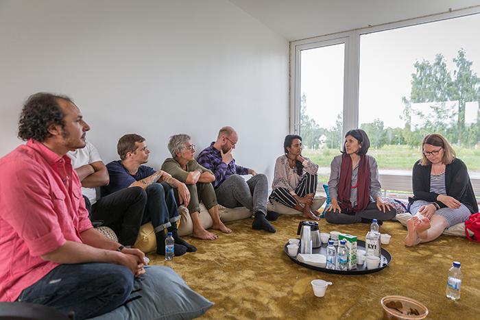 People sitting on the floor of a livingroom, talking.