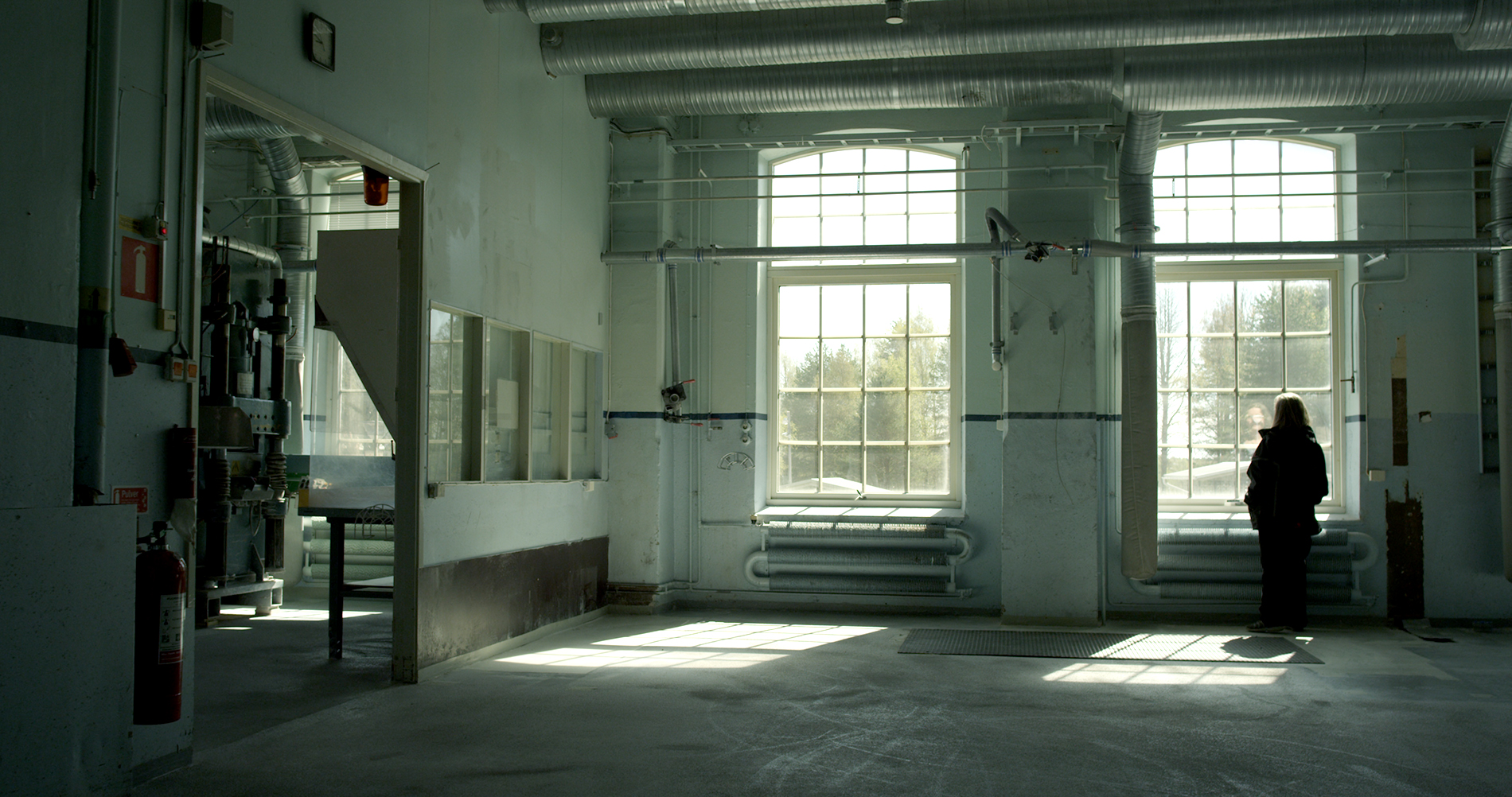 A single person in an empty room in the factory.