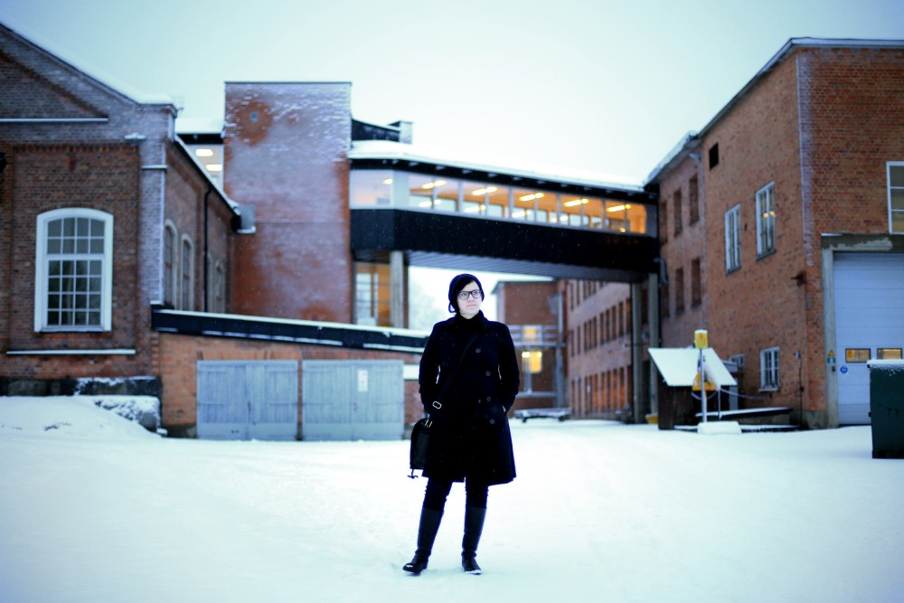Artist Sara Jordenö in front of a factory.