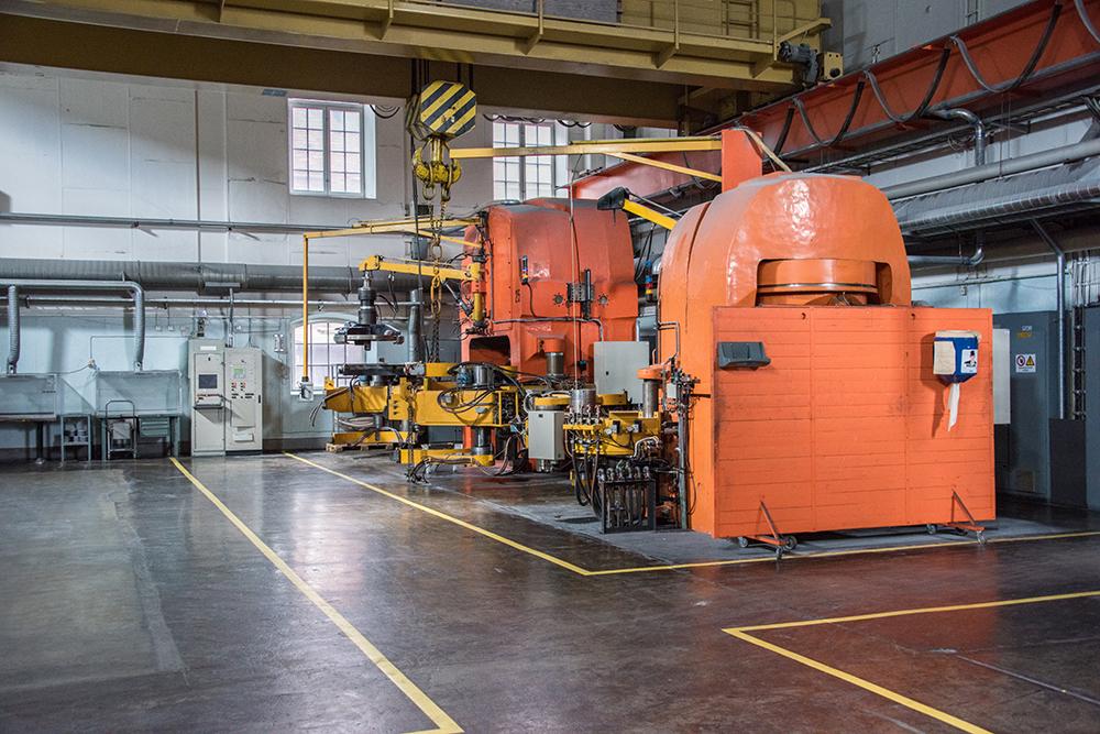 Inside a factory, with a big, orange, machine.