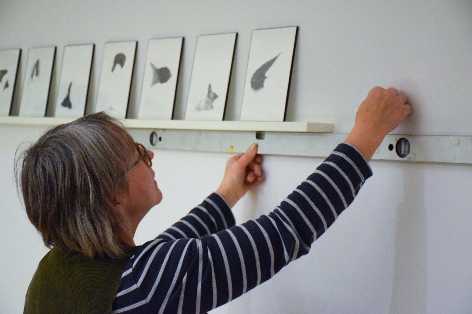An artcurator measures the space on the wall.