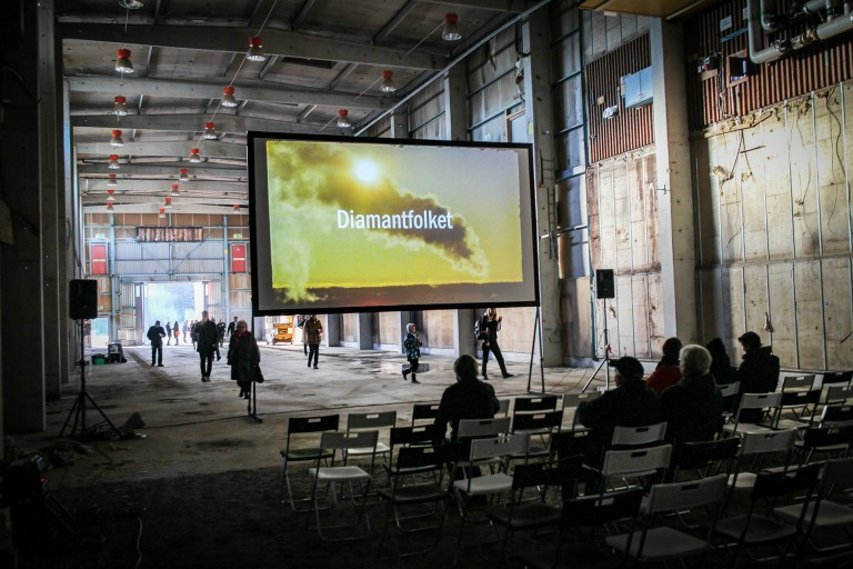 People watching a movie in an old factory.
