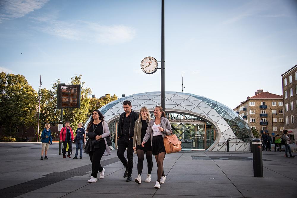 En grupp människor lämnar den glasöverbyggda utgången från station Triangeln. Ovanför deras huvuden ser man en vanlig offentlig klocka med texten