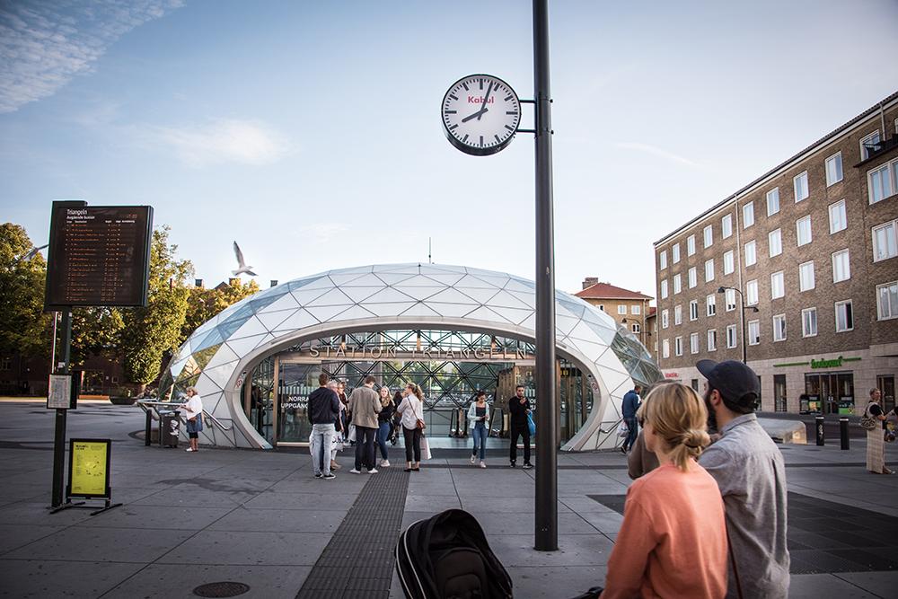 Folk går in och ut i den glasöverbyggda entrén till station Triangeln. Ovanför deras huvuden ser man en vanlig offentlig klocka med texten