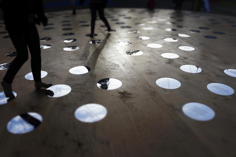 Trägolv med cirkulära speglar. Nisrine Boukhari, Imaginary Wholeness/Fragmentary Reality.