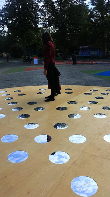 Någon står på ett runt trägolv med cirkulära speglar. I bakgrunden grus. Nisrine Boukhari, Imaginary Wholeness/Fragmentary Reality