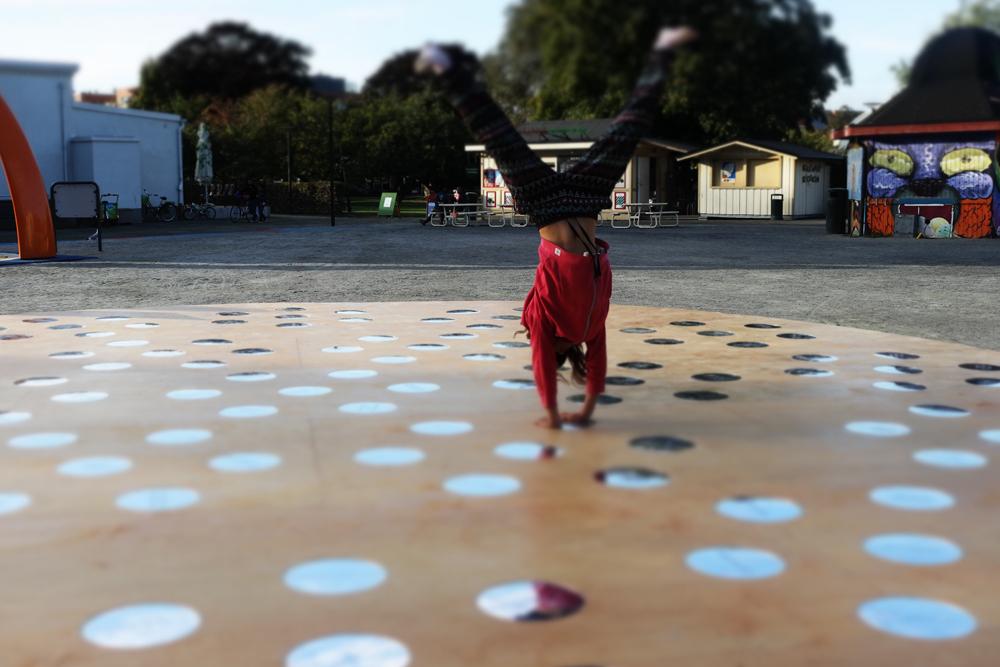 Någon står på händer på ett runt trägolv med cirkulära speglar. I bakgrunden grus. Nisrine Boukhari, Imaginary Wholeness/Fragmentary Reality.