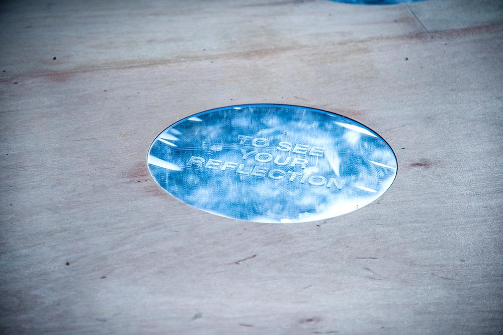 Detalj. Trägolv med en cirkulär spegel i vilken står den engelska texten: