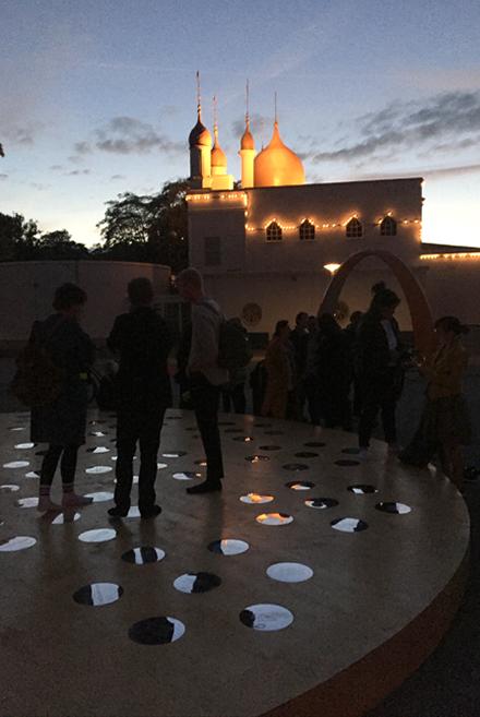 Flera personer på ett runt trägolv med små cirkulära speglar. Nisrine Boukhari, Imaginary Wholeness/Fragmentary Reality.