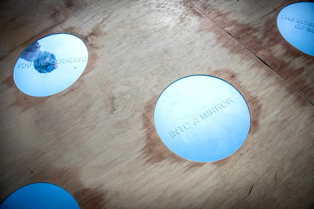 Detalj av ett trägolv, med två cirkulära speglar. I den ena ser man speglingen av en person. Där står texten:
