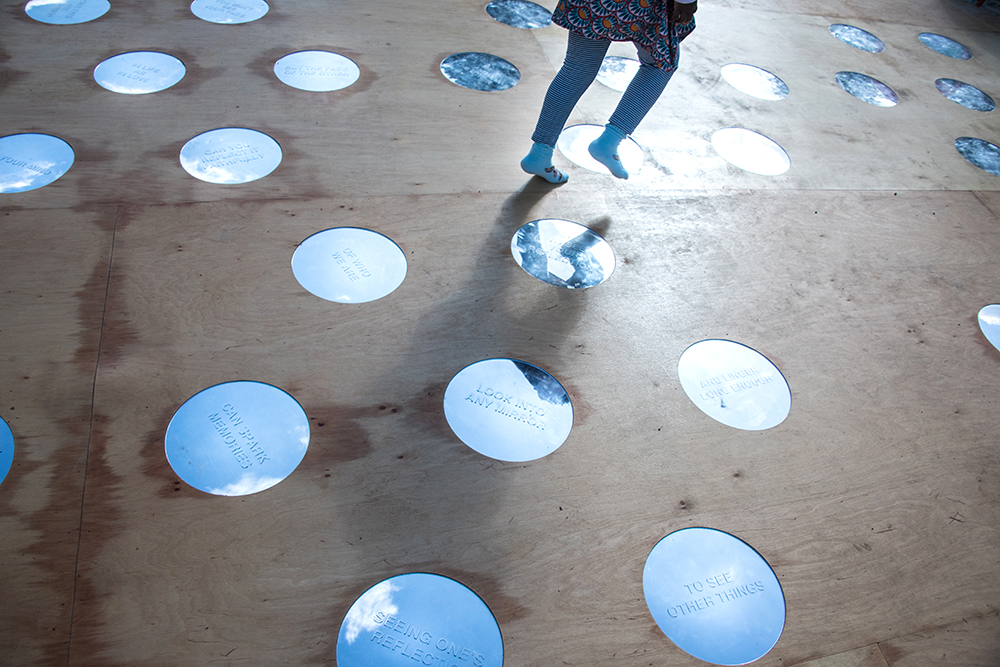 Del av ett trägolv med cirkulära speglar, i vilka himlen speglas. I den närmaste står texten:
