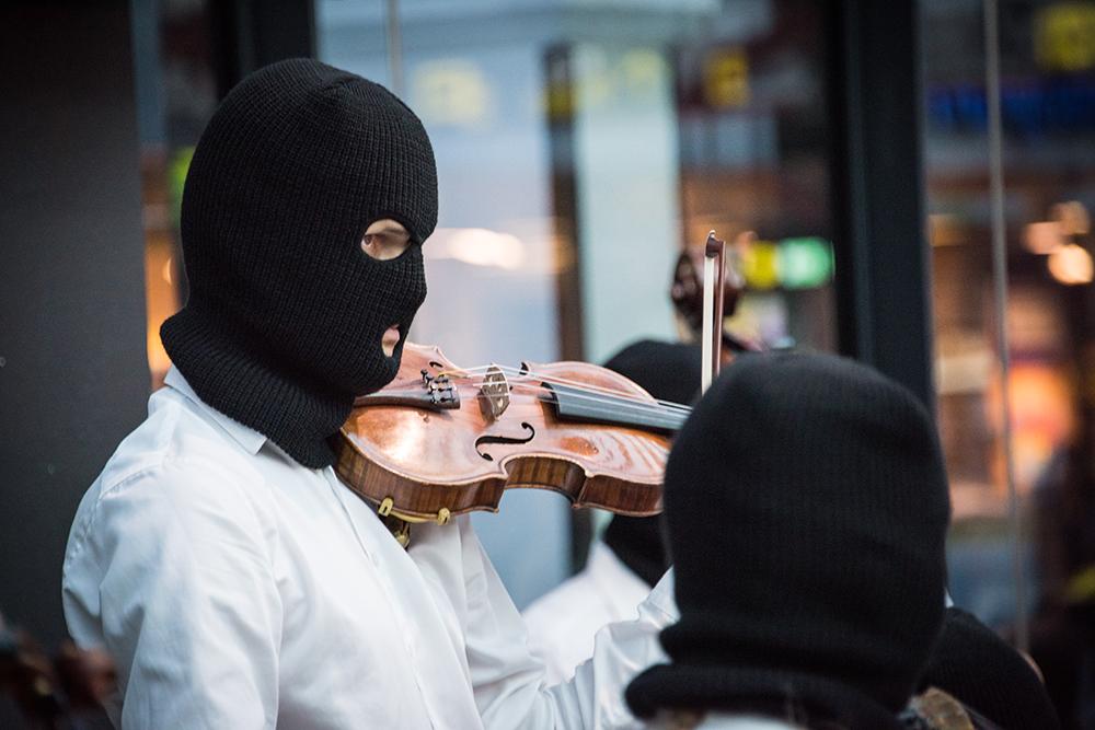 En violinist i svart heltäckande ansiktsmask, med hål endast för ögon och mun, står med fiolen på axeln och stråken lyft. Sislej Xhafa, Again and again.