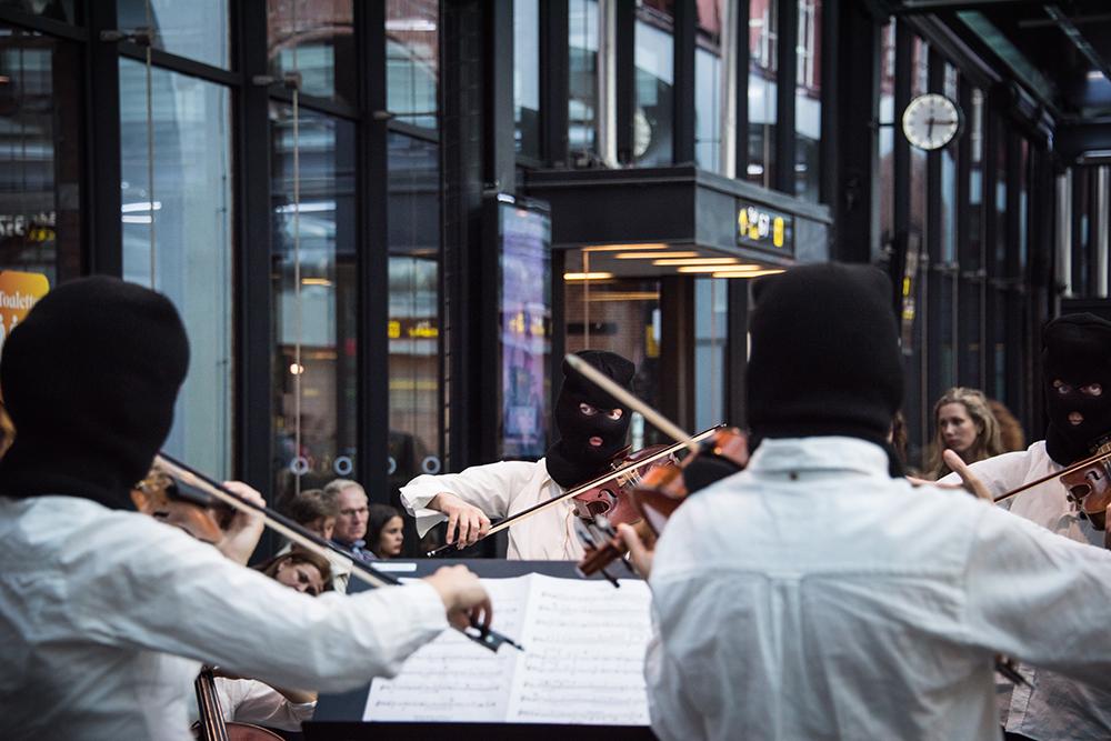 Flera violinister i vita skjortor och svarta ansiktsmasker som endast har hål för ögon och mun. Deras blickar möts över notstället medan de spelar. I bakgrunden publik. Sislej Xhafa, Again and again.