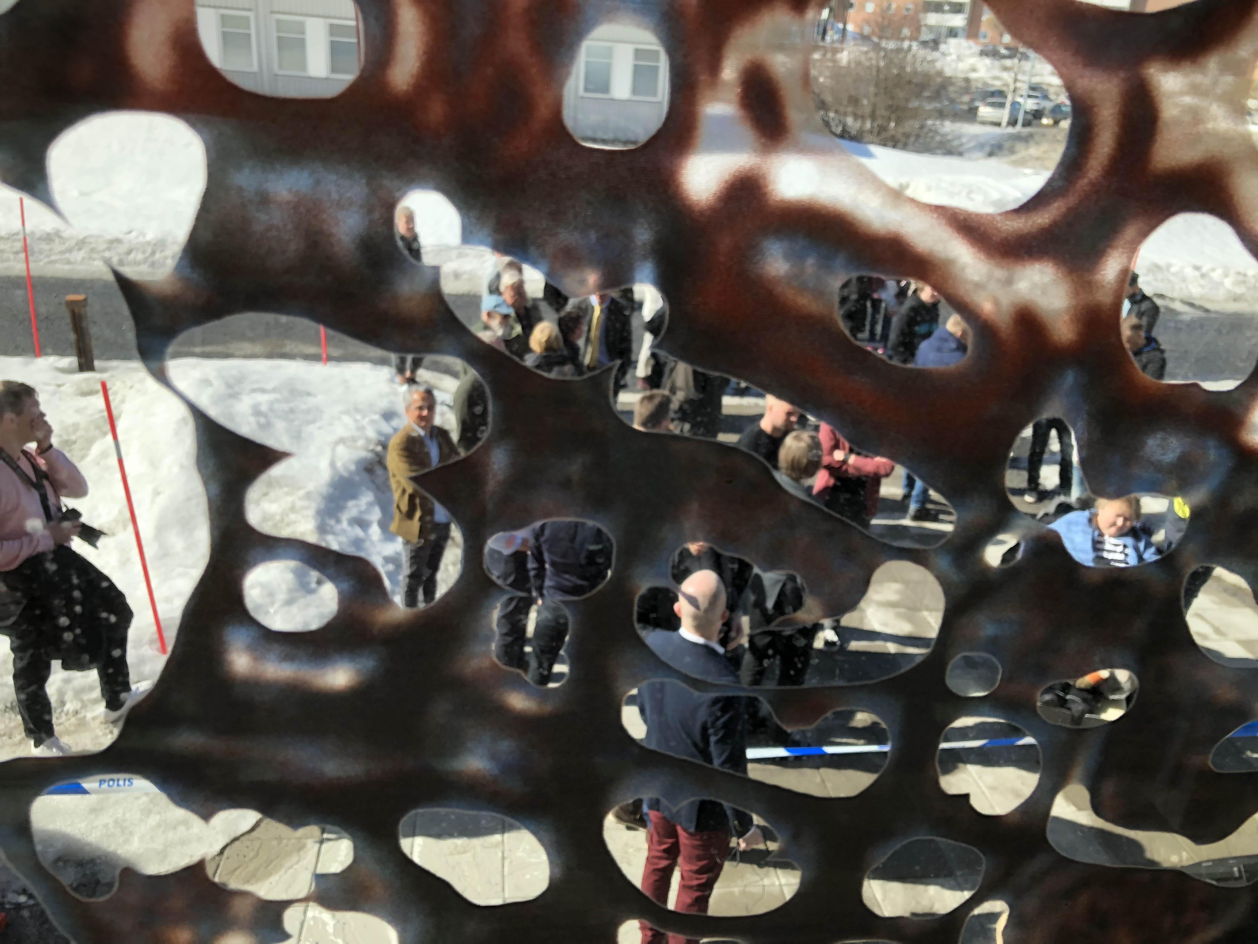 An image taken through the artworking looking at people below.
