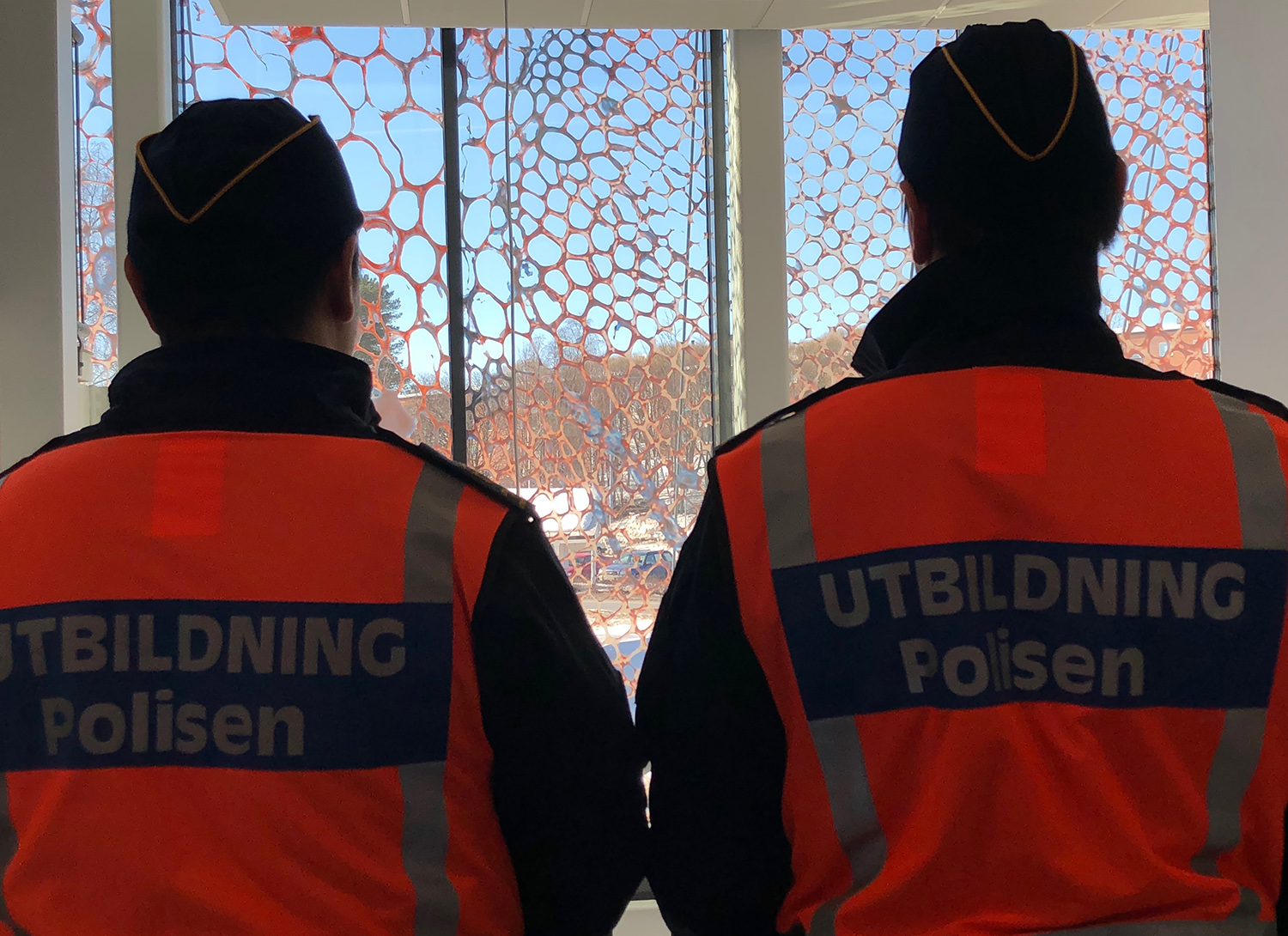 Two people with orange vests are looking at the artwork from the inside.