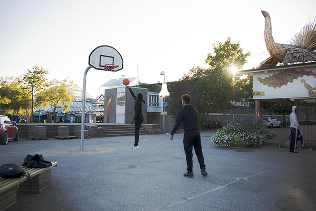 Two men playing basketball outside a house.