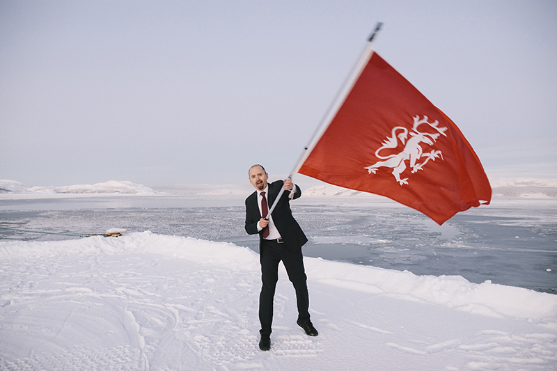 A man in a snowy landscape waves a red flag.