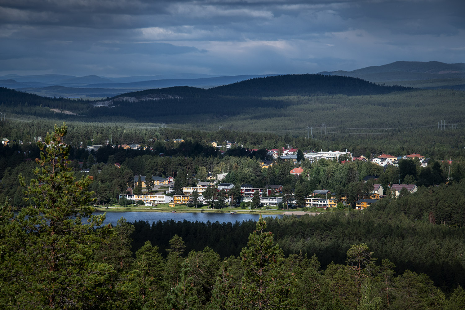 View over the Jokkmokk landscape with loots of pine trees, a lake, and a group of building.