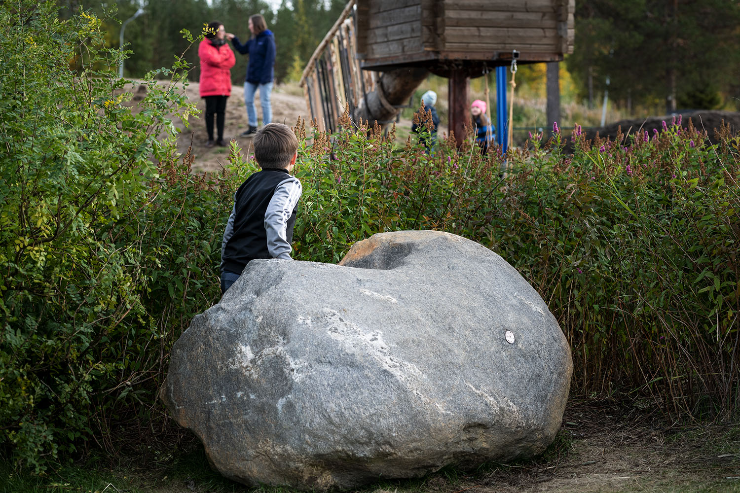 Small boy on a stone in front of a kindergarten.