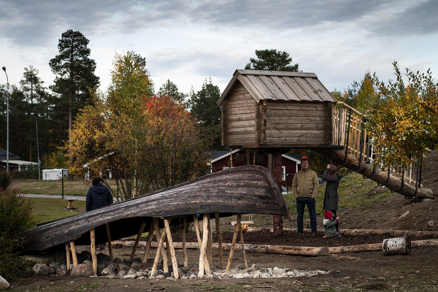 A yard at a kindergarten with a wooden boat piled on poles and a small shed also made by wood.