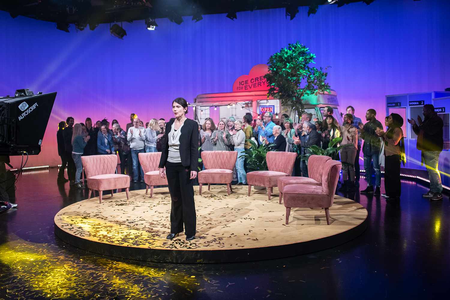 Audience in a TV-studio with a woman in the front.