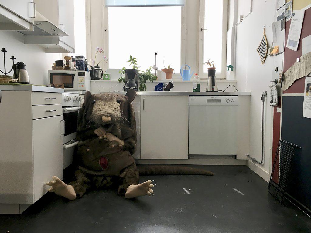 Scen ur pjäsen Vilka är ni med en råtta som sitter på golvet