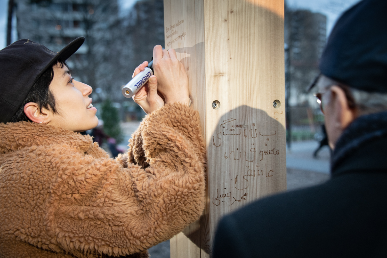 A woman engraving the post.
