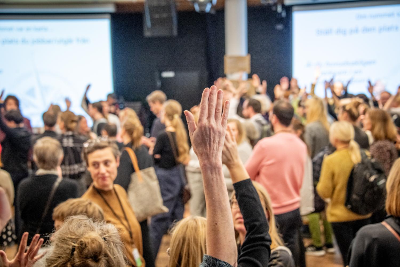 En hand som sträcks upp i förgrunden ett rum med människor i bakgrunden