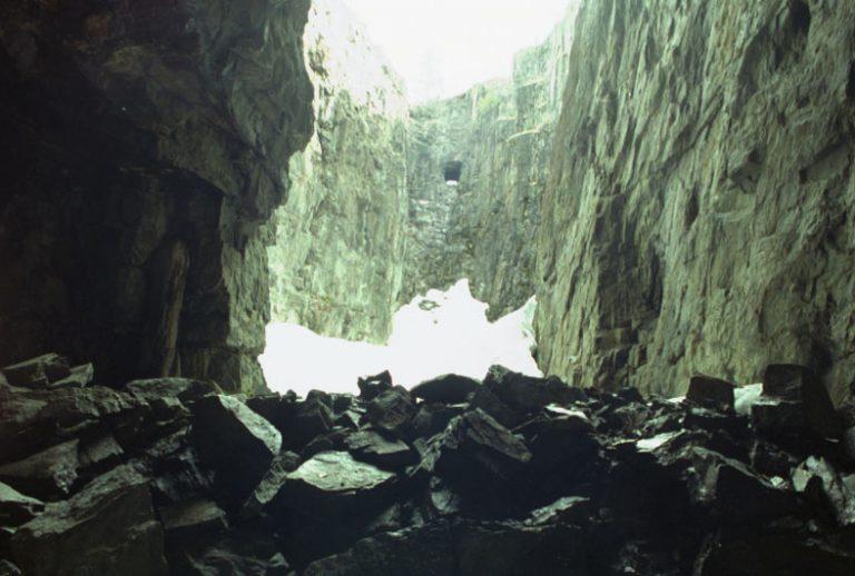 En bergmassa med block på marken och på sidorna lodräta klippväggar.